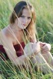 Schönes Mädchen in einem Gras Stockfoto