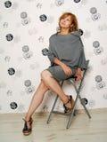 Schönes Mädchen in einem grauen Kleid in der Wohnung lizenzfreie stockfotografie