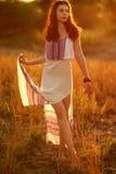 Schönes Mädchen in einem hellen Kleid bei Sonnenuntergang Stockfotografie