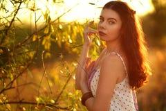 Schönes Mädchen in einem hellen Kleid bei Sonnenuntergang Stockfoto