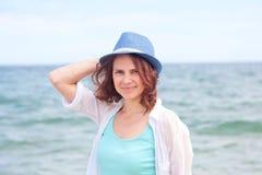 Schönes Mädchen in einem Hut auf einem Hintergrund des Meeres, im weichen focu Stockfoto