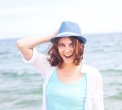 Schönes Mädchen in einem Hut auf einem Hintergrund des Meeres, im weichen focu Stockfotografie