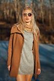 Schönes Mädchen in einem Mantel, der vor dem hintergrund einer Frühlingsnatur aufwirft stockbild