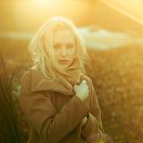 Schönes Mädchen in einem Mantel, der vor dem hintergrund einer Frühlingsnatur aufwirft lizenzfreies stockbild