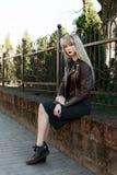 Schönes Mädchen in einem Park nahe einem Zaun Lizenzfreies Stockbild