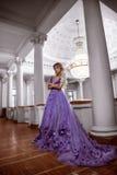 Schönes Mädchen in einem purpurroten Kleid Stockbild