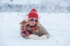 Schönes Mädchen in einem roten Hut und in einer Strickjacke im Schnee im Rosa mit Kopfhörern und Schal lizenzfreies stockbild