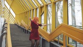 Schönes Mädchen in einem roten Kleidertanzen auf der Treppe stock video