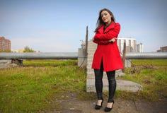 Schönes Mädchen in einem roten Mantel auf dem Hintergrund der Rohrleitung stockfotografie