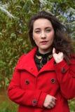 Schönes Mädchen in einem roten Mantel auf einem Hintergrund von Bäumen lizenzfreie stockbilder