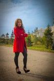 Schönes Mädchen in einem roten Mantel auf einer Parkgasse stockfotografie