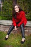 Schönes Mädchen in einem roten Mantel, der auf einem Ziegelsteingeländer sitzt stockbild