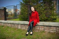 Schönes Mädchen in einem roten Mantel, der auf einem Ziegelsteingeländer sitzt stockfotos