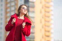 Schönes Mädchen in einem roten Mantel und in den Gläsern auf dem Hintergrund des Hauses stockfoto