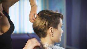 Schönes Mädchen in einem Schönheitssalon Berufsstilist macht der Frau einen neuen stilvollen Haarschnitt stock footage