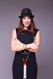 Schönes Mädchen in einem schwarzen Kleid und in einem Hut mit Tennisschläger stockfotos