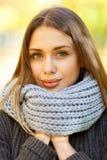 Schönes Mädchen in einem schwarzen Mantel auf einem Hintergrund des Herbstparks lizenzfreie stockfotos