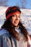 Schönes Mädchen in einem Skianzug und Schablone im Schnee lizenzfreies stockfoto