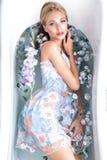 Schönes Mädchen in einem Sommerkleid im Badezimmer mit Blumen Schönes lächelndes Mädchen lizenzfreie stockbilder