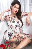 Schönes Mädchen in einem Sommerkleid im Badezimmer mit Blumen Schönes lächelndes Mädchen lizenzfreie stockfotos