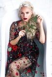 Schönes Mädchen in einem Sommerkleid im Badezimmer mit Blumen Schönes lächelndes Mädchen lizenzfreie stockfotografie