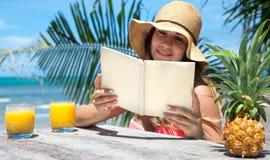 Schönes Mädchen in einem Strohhut ein Buch auf einem Hintergrund von Palmen und von Sommergetränk mit Ananas, auf dem Strand lese Lizenzfreies Stockfoto