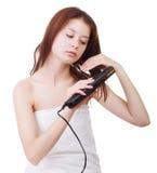 Schönes Mädchen in einem Tuch nach einer Dusche, mit idealer Haut, tut hairdress durch ein Haareisen Stockfoto