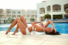 Schönes Mädchen in einem weißen Badeanzug ein Sonnenbad nehmend durch das Pool lizenzfreies stockfoto