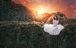 Schönes Mädchen in einem weißen Kleid, das im Garten bei Sonnenuntergang sitzt Mode, Hochzeit, Fantasiekonzept Lizenzfreies Stockfoto