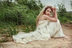 Schönes Mädchen in einem weißen Kleid sitzt auf dem Strand und schaut zurück Stockfotografie