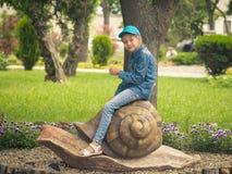 Schönes Mädchen in einer blauen Baseballmütze sitzt rittlings auf der Statue einer Schnecke im Park Lizenzfreie Stockfotos