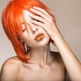 Schönes Mädchen in einer cosplay Art der orange Perücke mit den hellen kreativen Lippen Kunstschönheitsbild Stockfotos