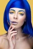 Schönes Mädchen in einer hellen blauen Perücke im Stil des cosplay und kreativen Makes-up Schönes lächelndes Mädchen Langes Belic Lizenzfreies Stockbild
