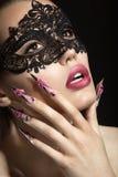 Schönes Mädchen in einer Maske mit den langen Fingernägeln Stockbild