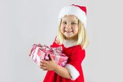 Schönes Mädchen in einer roten Kappe des neuen Jahres mit Geschenk Stockbild