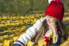 Schönes Mädchen in einer roten Kappe, die im Herbstlaub und in den Blicken in den Abstand, lächelnd liegt Stockbild