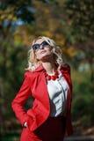 Schönes Mädchen in einer roten Klage im Herbst Stockbild
