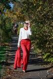 Schönes Mädchen in einer roten Klage im Herbst Lizenzfreie Stockfotografie