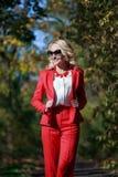 Schönes Mädchen in einer roten Klage im Herbst Stockfotografie