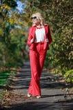 Schönes Mädchen in einer roten Klage im Herbst Lizenzfreies Stockbild
