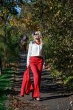 Schönes Mädchen in einer roten Klage im Herbst Lizenzfreie Stockfotos