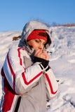 Schönes Mädchen in einer Skisportklage im Schnee stockfoto