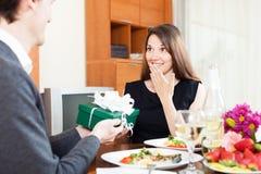 Schönes Mädchen empfängt ein Geschenk von einem Kerl Lizenzfreies Stockbild