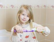 Schönes Mädchen erhält Zahnpasta auf einer elektrischen Zahnbürste Stockfotografie