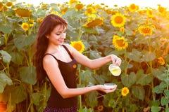 Schönes Mädchen gießt Sonnenblumenöl vom Pitcher stockbild