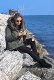 Schönes Mädchen Glückliche Frau, die zum Telefon auf dem Strand mit dem Meer im Hintergrund schaut lizenzfreie stockfotos