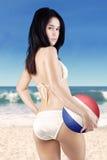 Schönes Mädchen hält einen Ball auf dem Strand Lizenzfreies Stockfoto