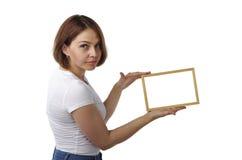 Schönes Mädchen hält einen hellen Holzrahmen Stockfotografie