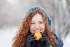 Schönes Mädchen hält Mandarine und lächelt im Freien Lizenzfreie Stockfotos