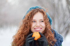 Schönes Mädchen hält Mandarine und schaut weg Stockfoto